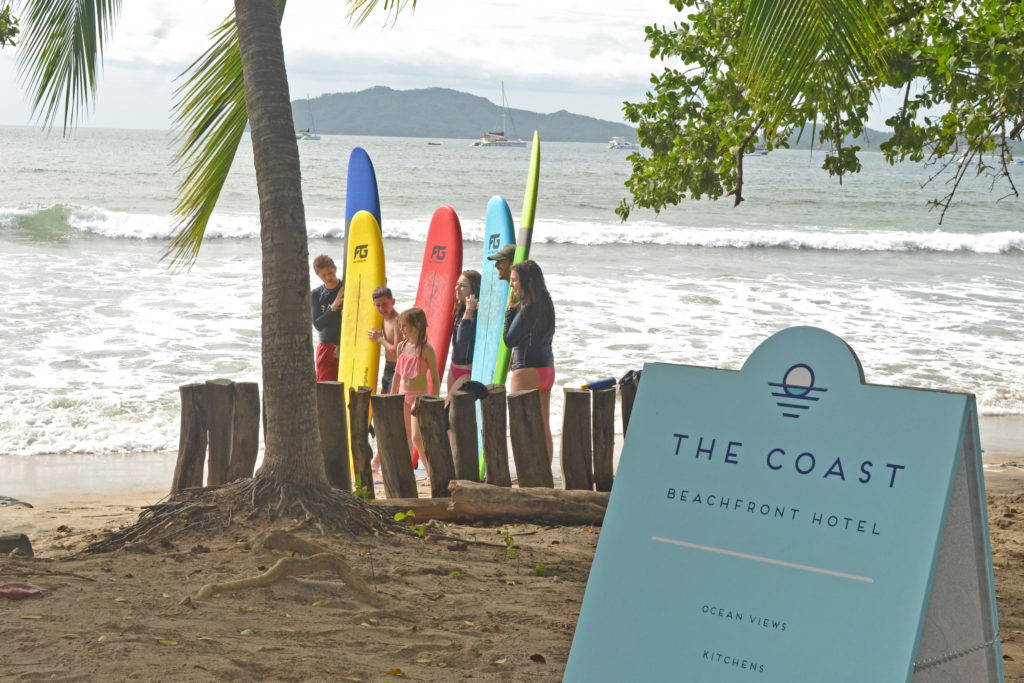 The Coat Hotel signage with surfers in the background