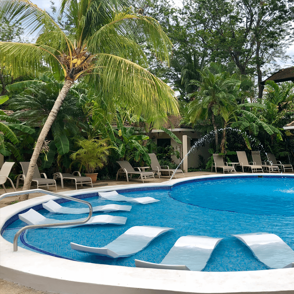 Poolside view with water fountain and seating