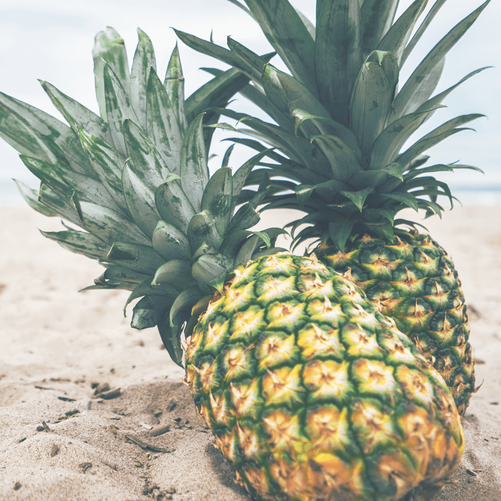 Two pineapples in the sand