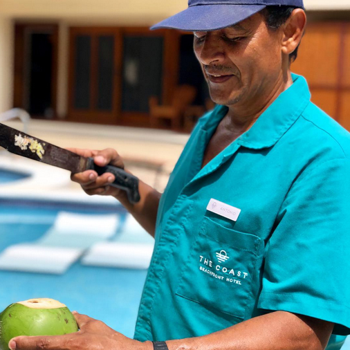 The Coast Beachfront Hotel employee, Antonio, cutting open a coconut for a guest