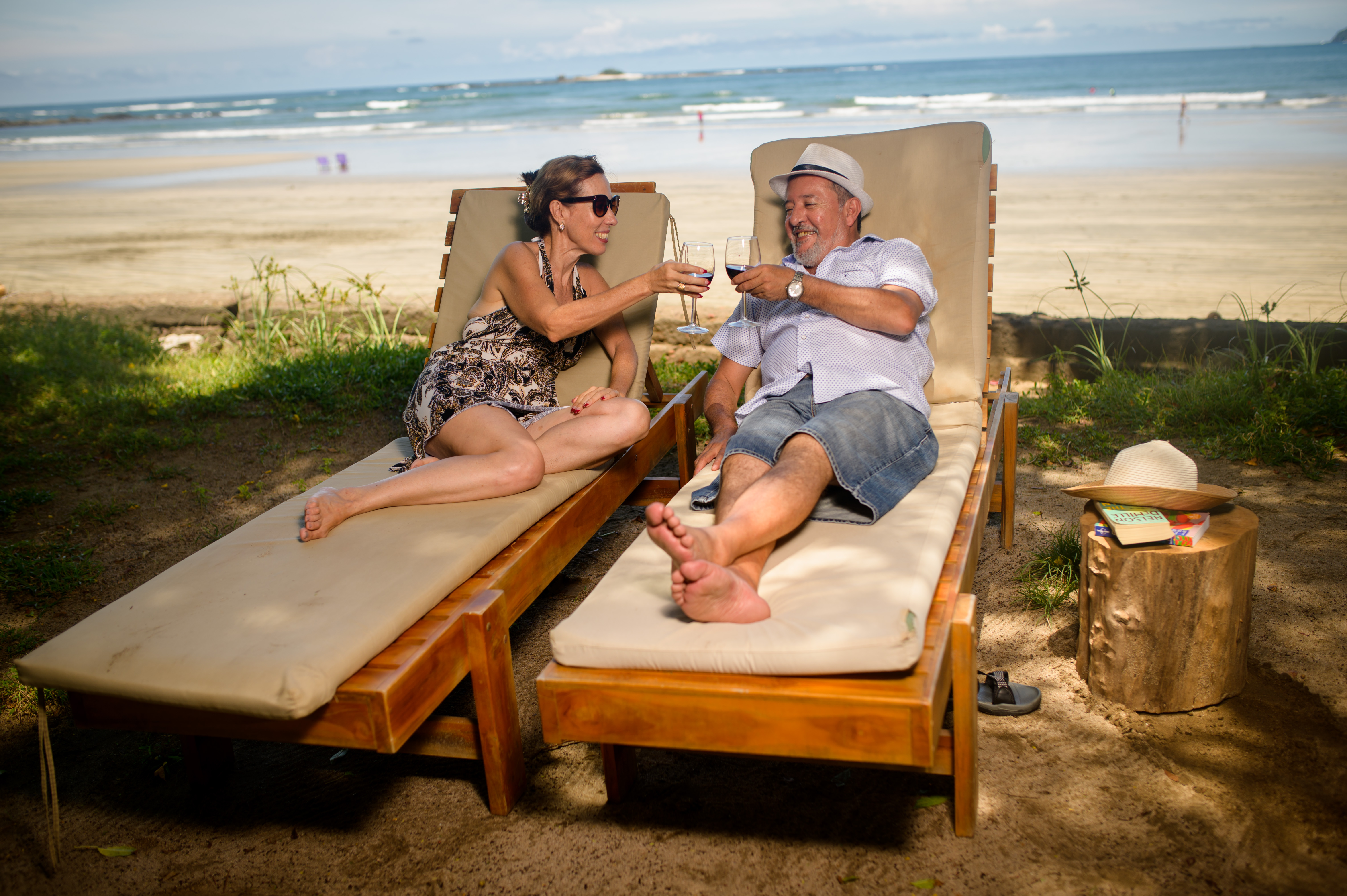 Couple toasting wine glasses on the beach