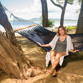 Person sitting on a hammock on the beach